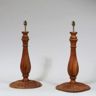 A PAIR OF CARVED WOODEN FLUTED BALUSTER CANDLESTICK LAMPS