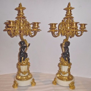 A 19th Century French pair of gilt and patinated bronze candelabra