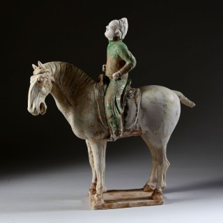 TANG DYNASTY STRAW AND GREEN GLAZED FIGURE OF AN EQUESTRIAN POLO PLAYER