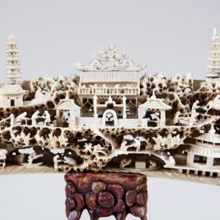CHINESE CARVING OF TEMPLES AMONG SHRUBBERY ON A CARVED WOODEN BASE