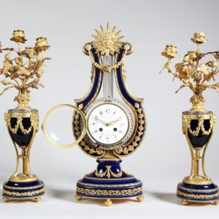 ORMOLU MOUNTED AND JEWELLED PORCELAIN CLOCK GARNITURE