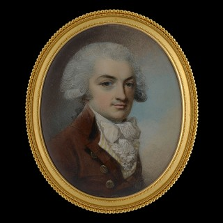A gentleman wearing a brown coat, yellow striped waistcoat, white cravat, frilled shirt and powdered wig, c. 1785