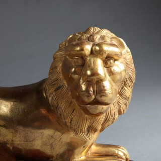 Two pairs of Empire period Sicilian giltwood models of couchant lions