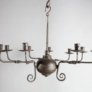 An Arts and Crafts black patinated nine branch Iron chandelier