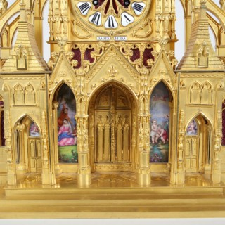 A GILT BRONZE CATHEDRAL CLOCK GARNITURE WITH PORCELAIN PLAQUES