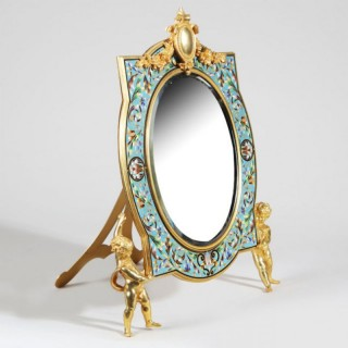 A CHAMPLEVÉ ENAMEL AND ORMOLU VANITY MIRROR HELD BY CHERUBS