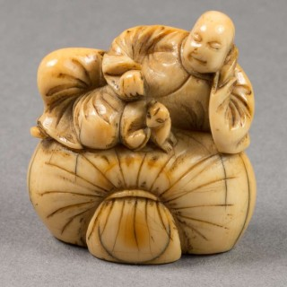 JAPANESE EDO PERIOD IVORY NETSUKE - MAN & DOG UPON TREASURE SACK