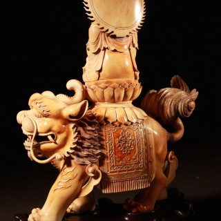 A magnificent and most impressive Chinese carved ivory okimono Of: Bodhisattva seated on a Buddhistic lion.
