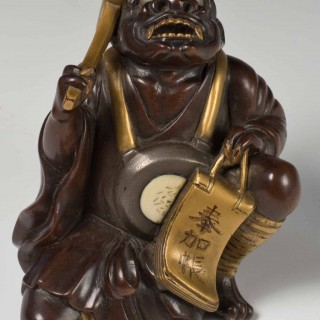 A FINELY CARVED JAPANESE HARDWOOD AND GOLD LACQUER ONI OKIMONO