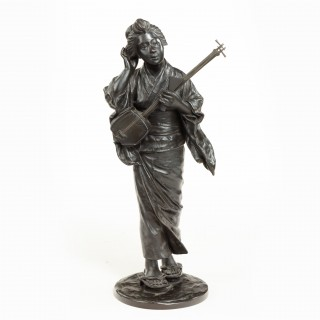 A Meiji period Japanese bronze bijin playing a samisen.