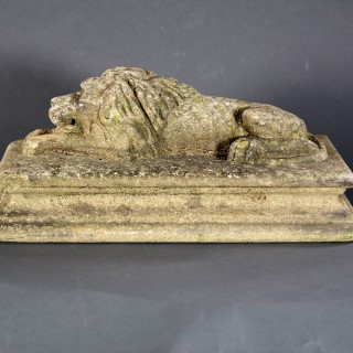 A 18TH CENTURY STONE RECUMBENT CARVED LION
