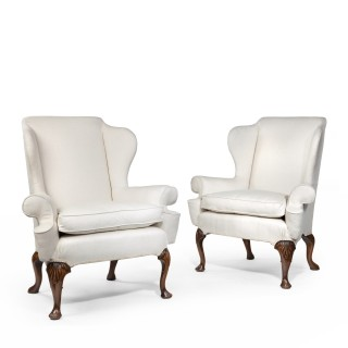 A pair of generous Queen Anne style walnut wing arm chairs