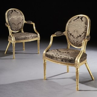 A Pair of George III Giltwood Armchairs in the manner of Mayhew & Ince
