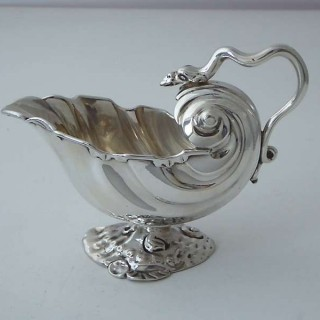 A rococo sauce-boat of shell form with snake handle on a single 'rocaille' foot, made in London in 1747