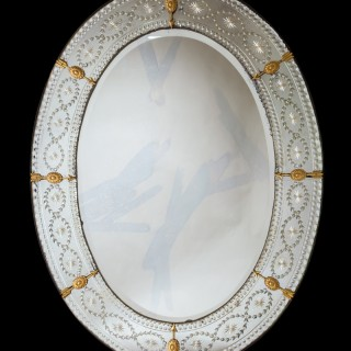 A LARGE OVAL CUT AND ENGRAVED GLASS MIRROR
