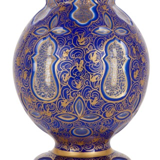 Two Bohemian Persian style jewelled and gilt blue glass jugs