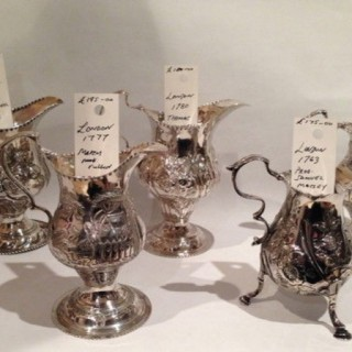 Antique silver cream jugs.
