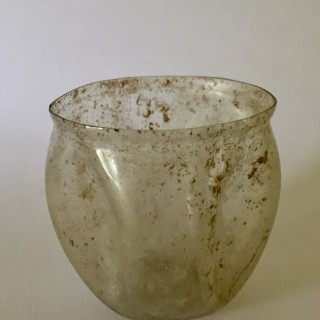 1st or 2nd century CE Roman glass cup with four indented panels.