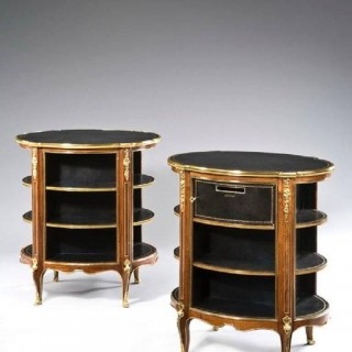 A pair of open library bookcases are inset with oval black leather tops