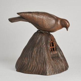A Japanese carved Wood Okimono of a Dove peering into a grain store.