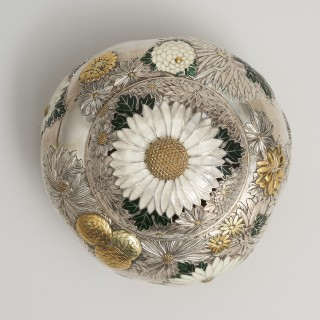 A Japanese silver and enamel koro decorated with large chrysanthemum blossoms.