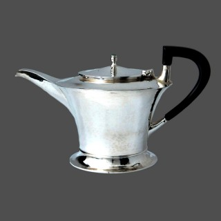 A striking A E Jones silver teapot with Ruskin finial