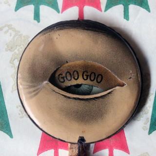 A Rare Late Victorian Novelty Mechanical Blinking 'Goo Goo' Pinback Badge c.1900