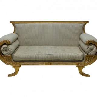 A FINE ENGLISH REGENCY REVIVAL GILTWOOD SETTEE