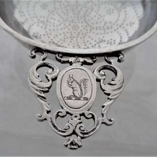 Lovely crested George II silver lemon strainer C1740