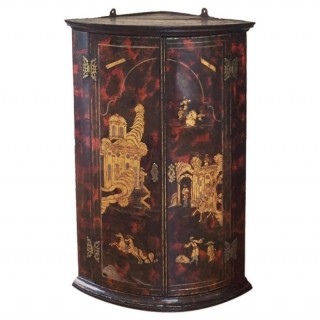 Queen Anne to George I red and black japanned chinoiserie corner cupboard.