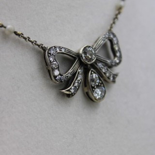 A fine Silver and High Carat Yellow Gold (tested), Victorian, Diamond Bow Pendant Circa 1880