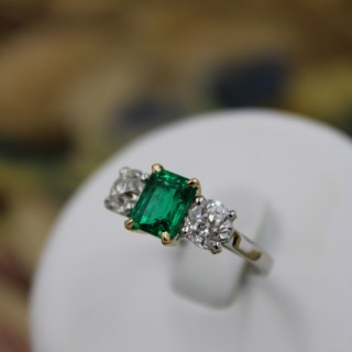 An exceptional Emerald and Diamond Three Stone Ring mounted in Platinum (Marked) and 18 Carat Gold, Pre-Owned.