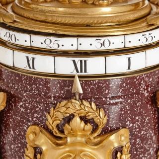 Gilt bronze mounted porphyry revolving dial mantel clock