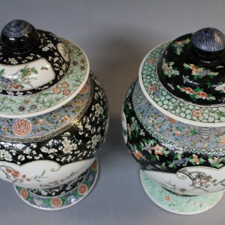 A matched pair of 19th century Chinese famille noir jars and covers