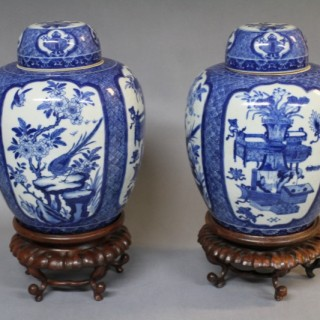 A pair of 19th century Chinese blue and white ginger jars and covers on wood stands