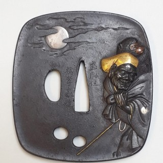 An antique Japanese iron tsuba decorated with a monkey trainer