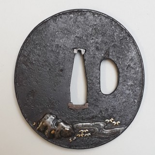 An antique Japanese iron tsuba decorated with a warrior and his pet dog