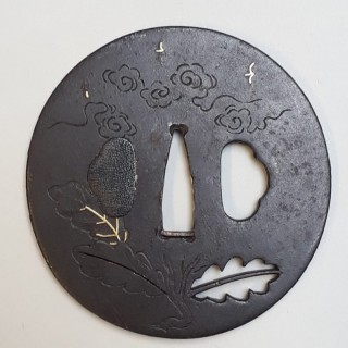An antique Japanese iron tsuba with pierced oak leaf design