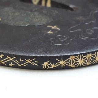 An antique Japanese iron tsuba with pierced oak leaf design