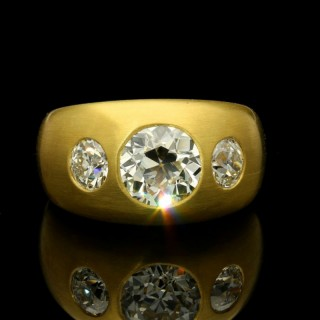 22ct gold satin-finish gypsy-set band ring set with three old mine cut diamonds.