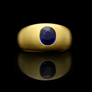 A 22ct yellow gold satin-finish gypsy-set band ring with a 2.60ct sapphire cushion.