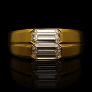 A double emerald-cut diamond ring in 22ct yellow gold gypsy setting.