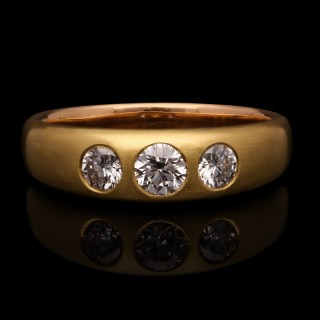 An 18ct gold and round brilliant diamond gypsy-set three stone ring with satin finish.