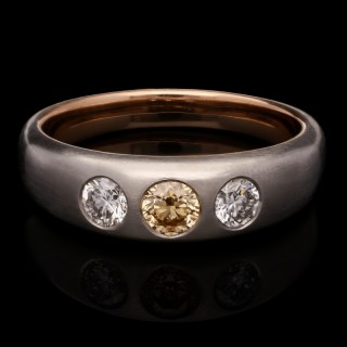 A platinum and gold fancy orange diamond and diamond gypsy-set ring with satin finish.