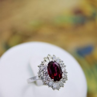 A very fine 18 Carat White Gold (tested) Oval Natural Untreated Siam Ruby (1.71 Carats) and Diamond Cluster Ring, Circa 1970.
