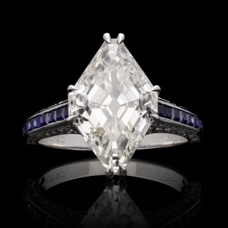 An unusual 5.31ct lozenge shaped diamond ring set in platinum with sapphire and diamond set band.