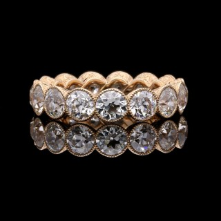 A  full diamond eternity ring set with 4.90cts of old European cut diamonds in rose gold.