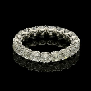 A full circle eternity ring set with old mine cushion shaped diamonds in platinum.