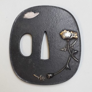 An antique Japanese Iron tsuba with poppy decoration