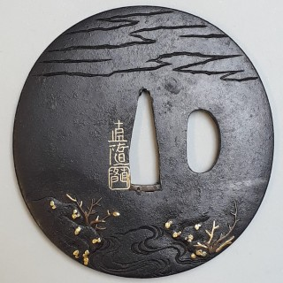 An antique Japanese iron tsuba with multimetal decoration of a reed cutter